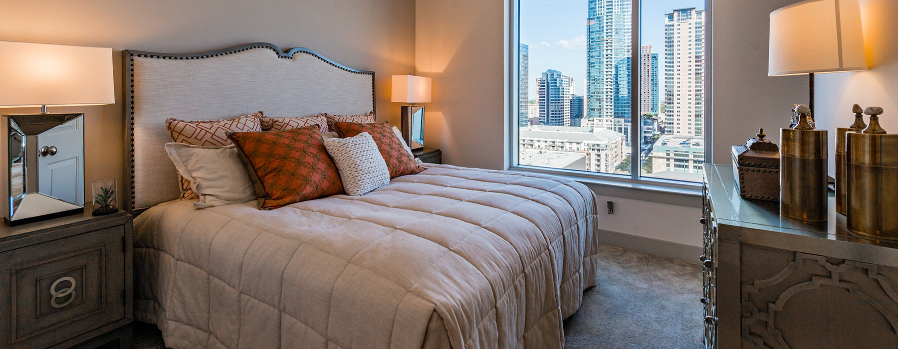 Spacious and well lit bedroom with plush carpet and large windows